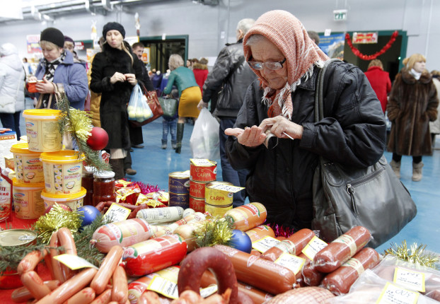A woman counts money at a food fair in the village of Ulyanovka, south-east of Stavropol, Russia December 22, 2015. REUTERS/Eduard Korniyenko - RTX1ZRCH