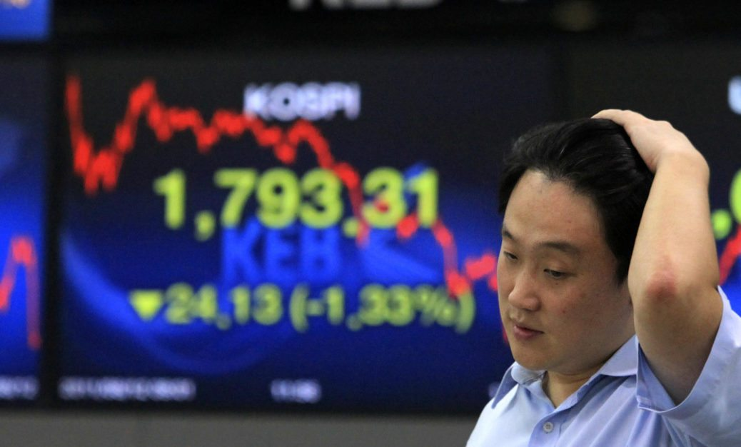 A currency trader works in front of  a screen showing the Korea Composite Stock Price Index at the Korea Exchange Bank headquarters in Seoul, South Korea, Friday, Aug. 12, 2011.  Asian stock markets struggled to find their footing Friday, giving back morning gains despite a dramatically higher finish on Wall Street prompted by a slight drop in U.S. unemployment claims. The Korea Composite Stock Price Index fell 1.33 percent, or 24.13, to close at 1,793.31.(AP Photo/Ahn Young-joon)